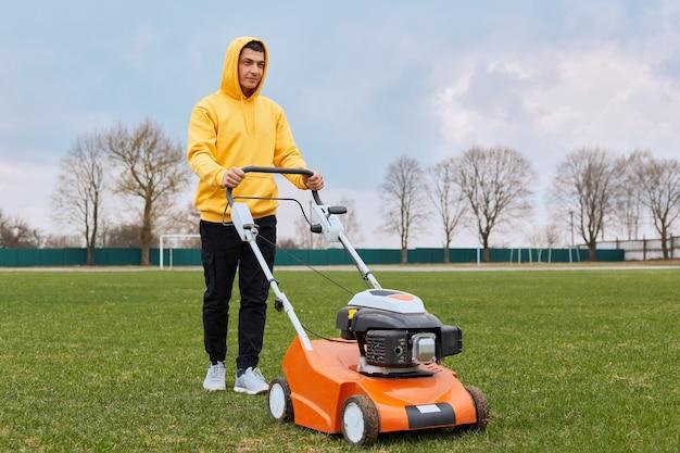 彼の手にガソリン芝刈り機と黄色のパーカーと黒のズボンで物思いにふけるハンサムな男は芝生の草を刈る