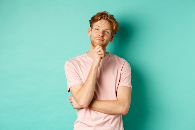Pensive handsome man with red hair and beard looking at upper left corner, making choice and looking thoughtful, standing in t-shirt over mint background.