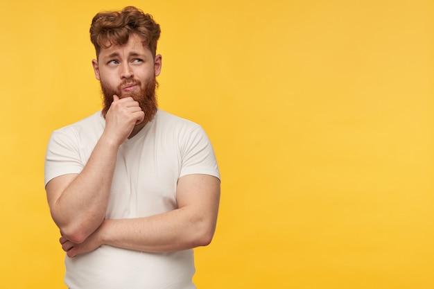 あごに触れている空白のtシャツを着た物思いにふけるハンサムな若いひげを生やした男は、思慮深い表情で脇に見えます