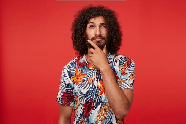 Задумчивый красивый молодой брюнет кудрявый мужчина с бородой, держащий подбородок поднятой рукой и задумчиво смотрящий в сторону, щурясь и морща лоб, стоя на красном фоне