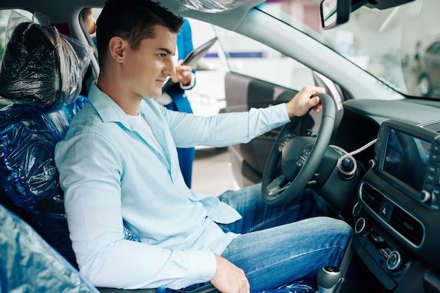 생각에 잠긴 잘생긴 청년은 대리점에서 새 차에 앉아 편안한 구획을 즐기고 있습니다.