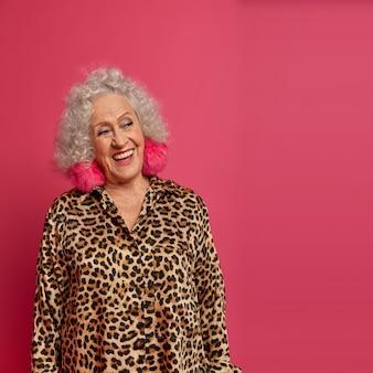 Pensierosa donna anziana felice felice di essere in pensione, sembra positivamente a parte, ha i capelli ricci, il trucco e la faccia rugosa, indossa abiti eleganti, incontra gli ospiti durante il suo compleanno o la festa di pensionamento