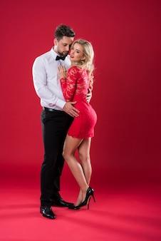 赤い背景に物思いにふける異性愛者のカップル