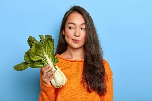 物思いにふける主婦は緑のチンゲン菜を持って、この有用な野菜から何を調理するかを考え、食事を続け、菜食主義者であり、オレンジ色のジャンパーを着ています
