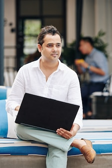Pensive indian businessman with laptop