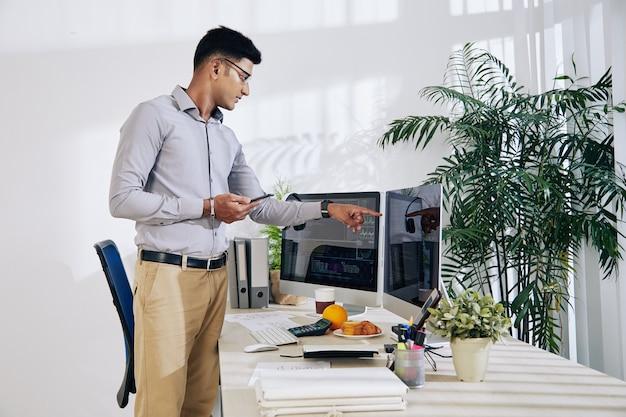 スマートフォンを手に、プログラミングコードが書かれたコンピューター画面を指している物思いにふけるインドのプログラマー