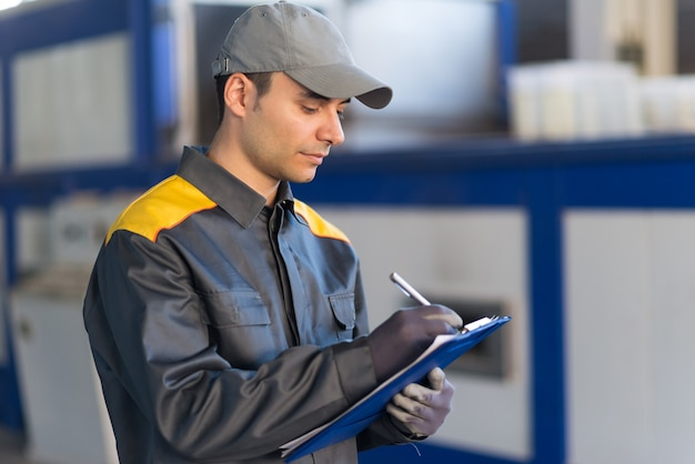 Pensive industrial worker writing on a document
