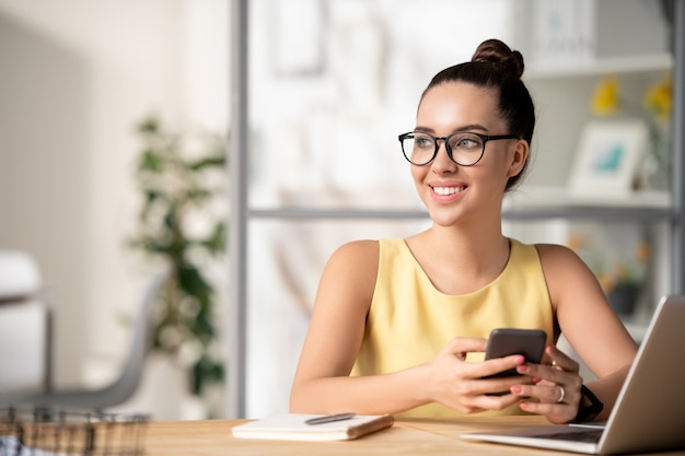 Pensive inspired creative manager in eyeglasses sitting at desk with laptop and checking phone in office