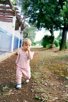 物思いにふける子供が家の近くの柵を通り過ぎて小道を歩く