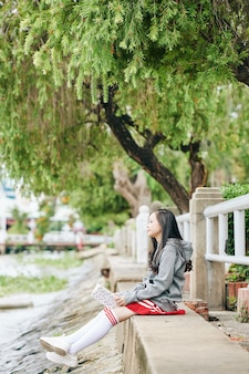 Pensive korean schoolgirl with book in hands sitting on river bank and looking at water