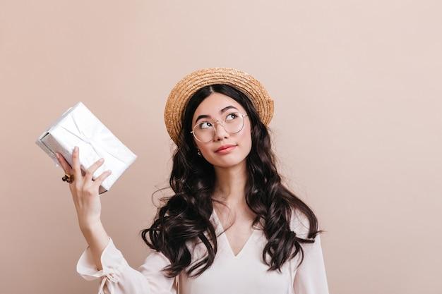 Задумчивая корейская женщина, держащая настоящую коробку. студия сняла мечтательную китайскую девушку с подарком.