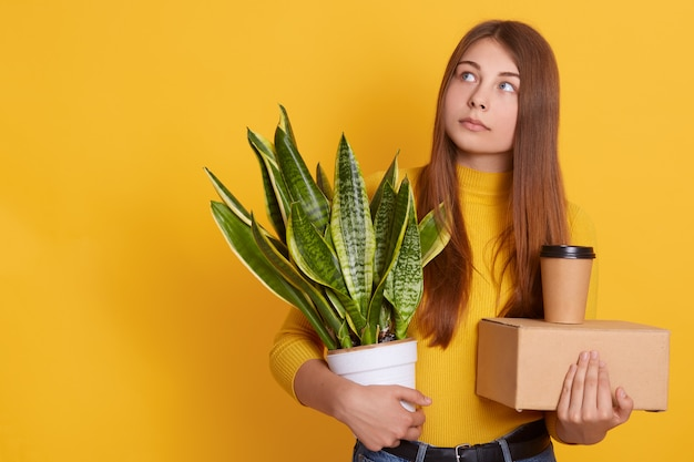 Pensive lady dresses casual clothing holding her staff and flowerpot in hands, looking aside, thinks about her dismissal, being sad, looks thoughtful, standing isolated over yellow wall.