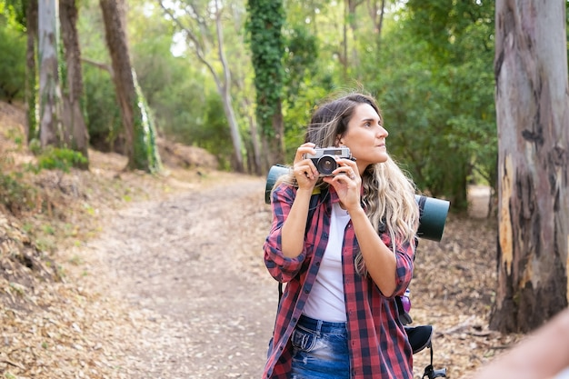 Pensive lady holding camera, looking around and standing on road. female tourist exploring nature and taking photo of forest. tourism, adventure and summer vacation concept
