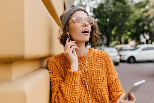 Pensive lady in stylish glasses looking up enjoying good autumn weather