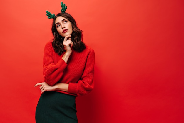 Pensive lady with brunette hair in red sweater and green skirt looking away on isolated wall