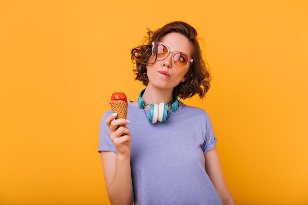 Signora pensierosa con l'acconciatura riccia in posa con il gelato. tiro al coperto di meravigliosa ragazza bianca in occhiali alla moda in piedi.