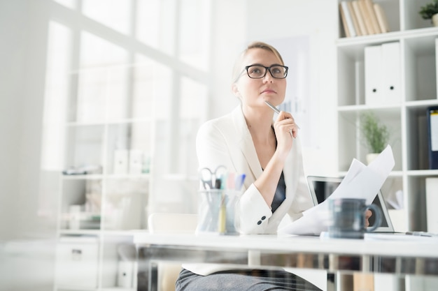 Pensive lady working with papers in office