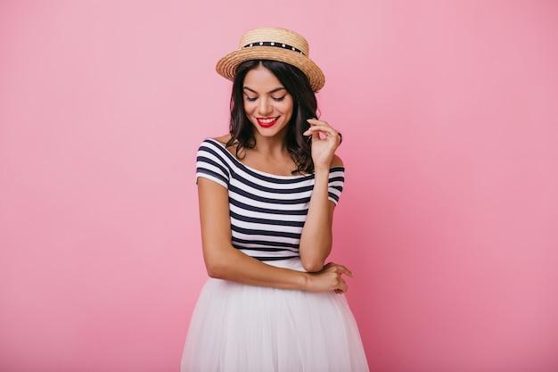 Задумчивая смеющаяся девушка в соломенной шляпе, глядя вниз во время фотосессии. портрет романтичной дамы брюнет в белой юбке.
