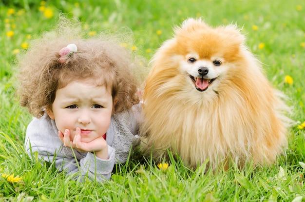 Задумчивая маленькая красивая девушка лежит на траве с собакой
