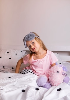 A pensive little blonde girl in pajamas is sitting on the bed linen with a soft toy on the bed in the room
