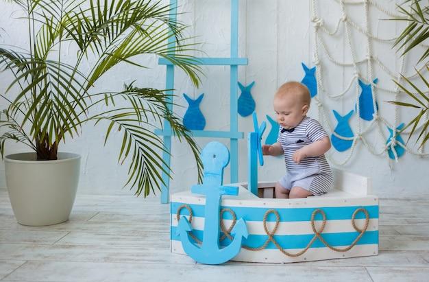 物思いにふける小さな男の子は海の装飾が施された壁に青と白の木製ボートに座っています
