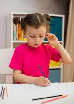 잠겨있는 어린 소녀는 방에있는 테이블에 종이에 색연필로 그립니다.