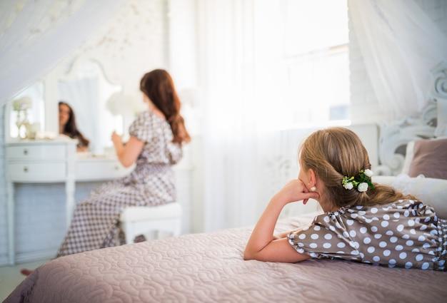 長いドレスを着た物思いにふける少女がベッドに横になり、長いドレスを着た若い母親が彼女を補う