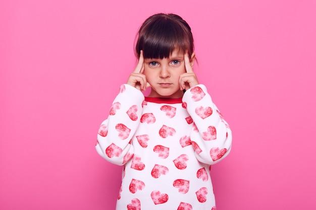 カメラを見て物思いにふける少女は、重要なことを考え、寺院の近くに指を置き、思慮深く集中し、ピンクの壁に隔離されています。