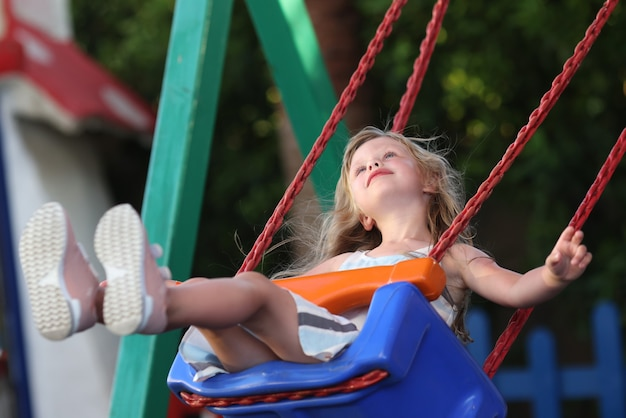 Pensive little girl ride swing and look up. child in dress sit on attraction and dream.