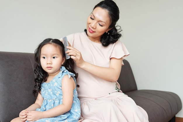 Pensive little girl sitting on sofa when mother combing her curled hair