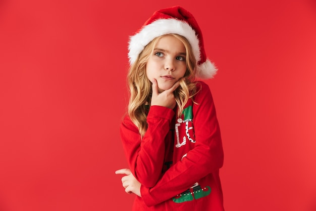Задумчивая маленькая девочка в рождественском костюме стоя изолирована