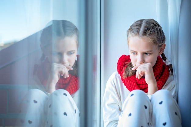 A pensive little girl with a scarf around her neck sits on the windowsill and is reflected in the window. loneliness concept.