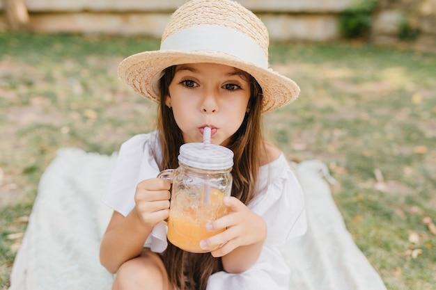 白いリボンと夏の帽子の物思いにふける小さな女性はオレンジジュースを飲み、目をそらします。公園で毛布にカクテルを楽しんでいる茶色の髪の少女の屋外の肖像画。