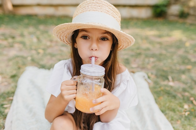 Pensive little lady in summer hat with white ribbon drinks orange juice and looking away. outdoor portrait of brown-haired girl enjoying cocktail on blanket in park.