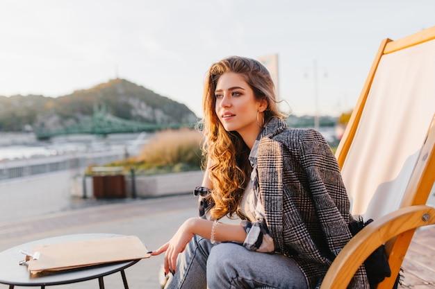 Pensieroso ragazza dai capelli lunghi in blue jeans in attesa del suo ordine in un caffè all'aperto