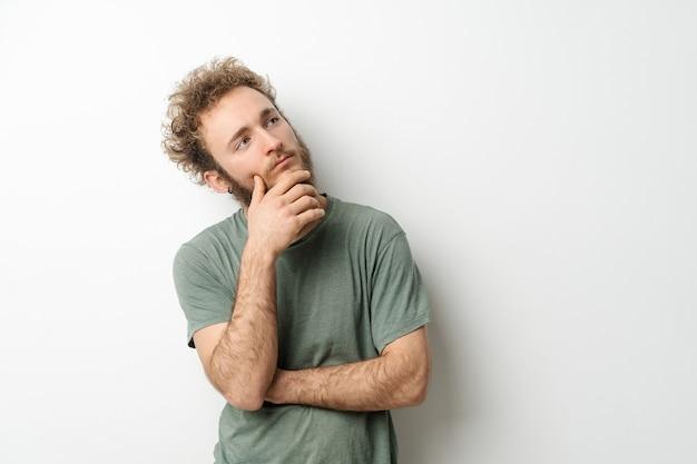 Задумчивый взгляд красивого молодого человека с вьющимися волосами в оливковой футболке, смотрящего вверх