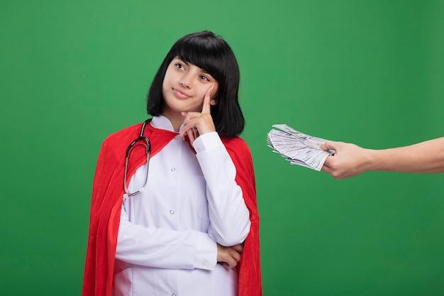 物思いにふける側の若いスーパーヒーローの女の子が医療用ローブと聴診器を身に着けている頬に指を置き、緑に隔離された彼女にお金を与える誰かをマント