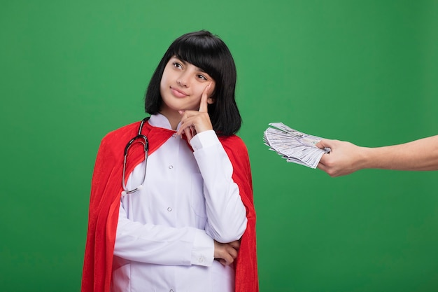 Pensive looking at side young superhero girl putting finger on cheek wearing stethoscope with medical robe and cloak someone giving money to her isolated on green