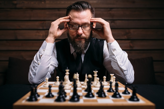 Pensive male chess player in glasses thinking about game strategy.