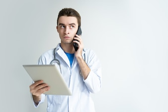 Pensive male doctor using tablet computer and smartphone