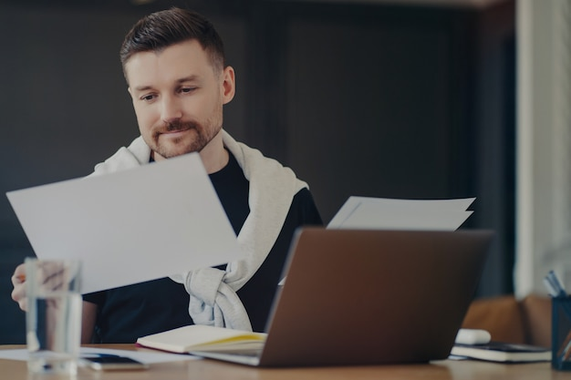Pensive male freelancer or manager in casual clothes analyzing project documents and thinking about business, doing paper work while sitting at his workplace with laptop computer, working from home