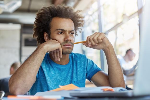 작업하는 동안 최선을 다하기 위해 노력하는 서류와 함께 작업 노트북에서 심각한 표정으로 찾고 커피 숍에 앉아 잠겨있는 남성 프리랜서. 연필로 바쁜 대학 어두운 피부 학생