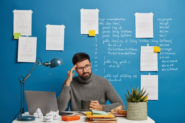 Pensive male social media marketing specialist turns away, keeps hand on temple, feels tired of long hours of work, drinks coffee, sits in coworking space.
