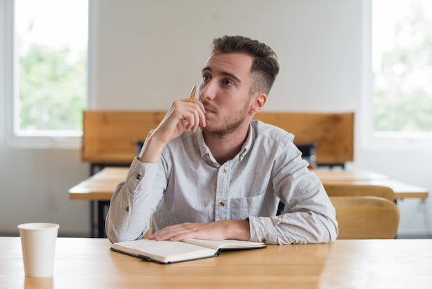 Pensive male student sitting at desk in classroom