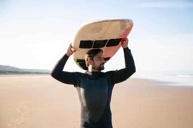 Задумчивый мужчина-серфер держит доску для серфинга на голове и смотрит на море