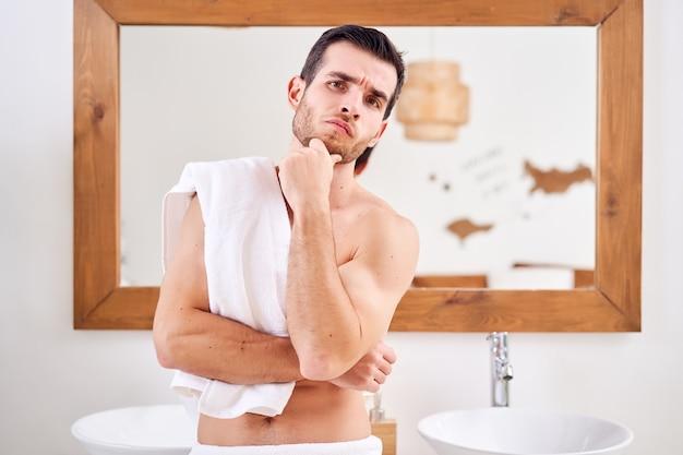 朝、お風呂の鏡の近くに立っている肩にタオルを持った物思いにふける男性