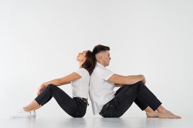 Задумчивый мужчина и женщина, сидящие спиной к спине после ссоры на белом