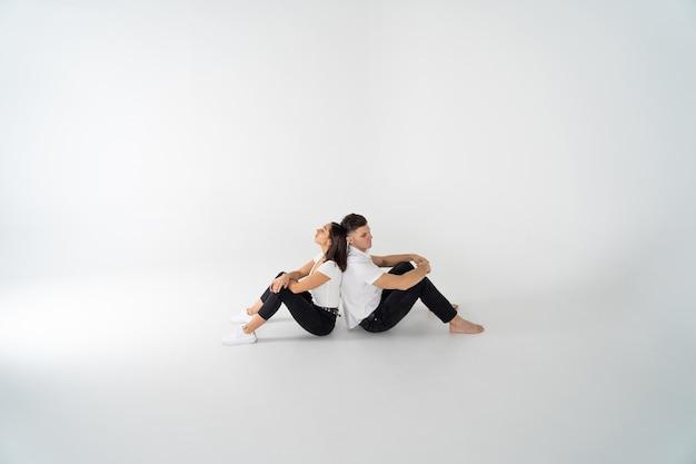 Задумчивый мужчина и женщина сидят спиной к спине после ссоры