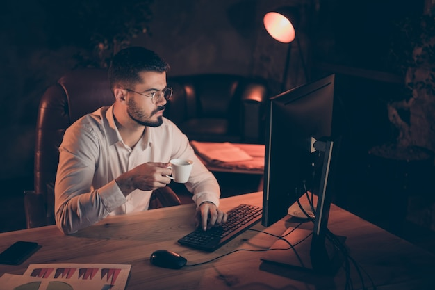 Pensive man of business holding cup of hot beverage typing pc