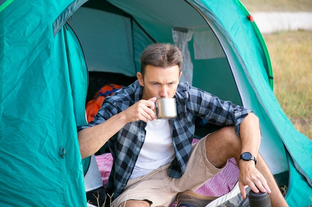 Pensive man drinking tea, sitting in tent and looking away. caucasian handsome traveler camping on lawn in park and relaxing on nature. backpacking tourism, adventure and summer vacation concept